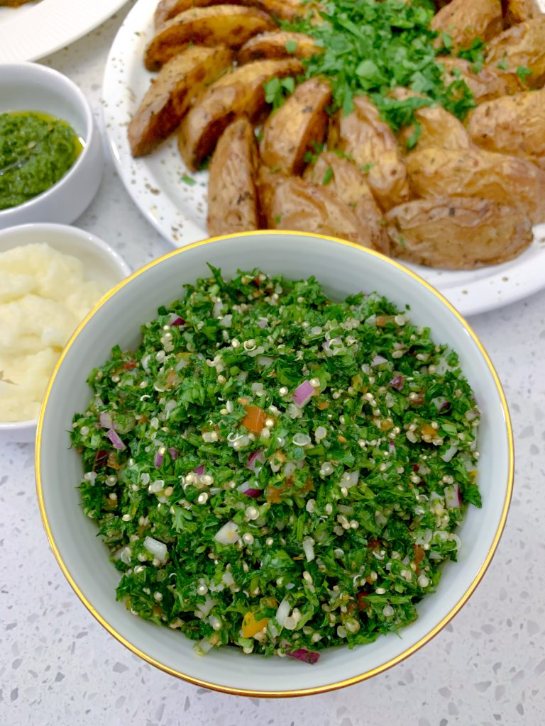 A bowl of bright green, fluffy quinoa tabbouleh.